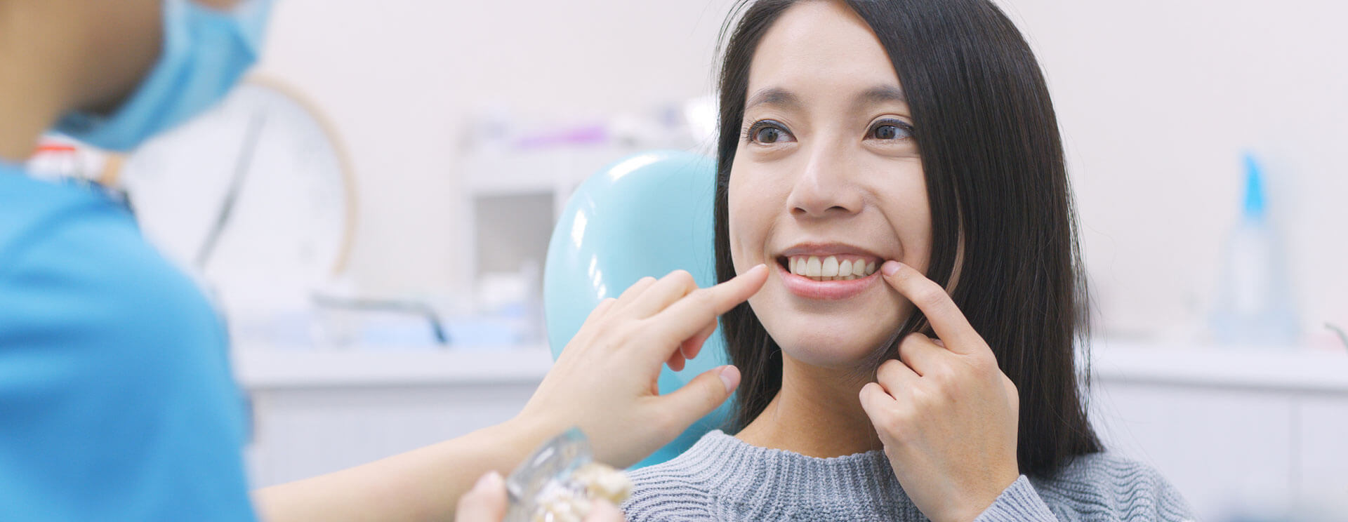 Female patient smiling and pointing her finger showing a dental implant