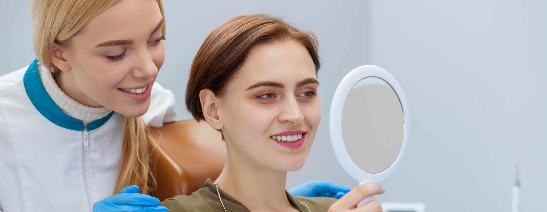 Female patient checking her teeth using a hand mirror after dental treatment