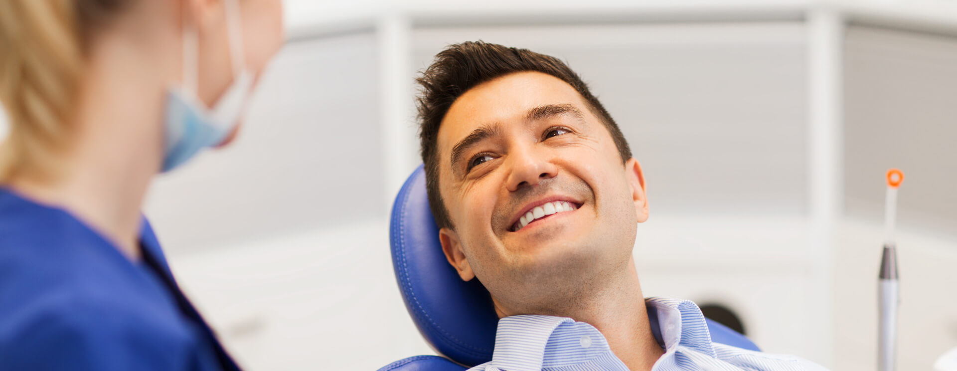 Male person seated on dental chair smiling with assistant