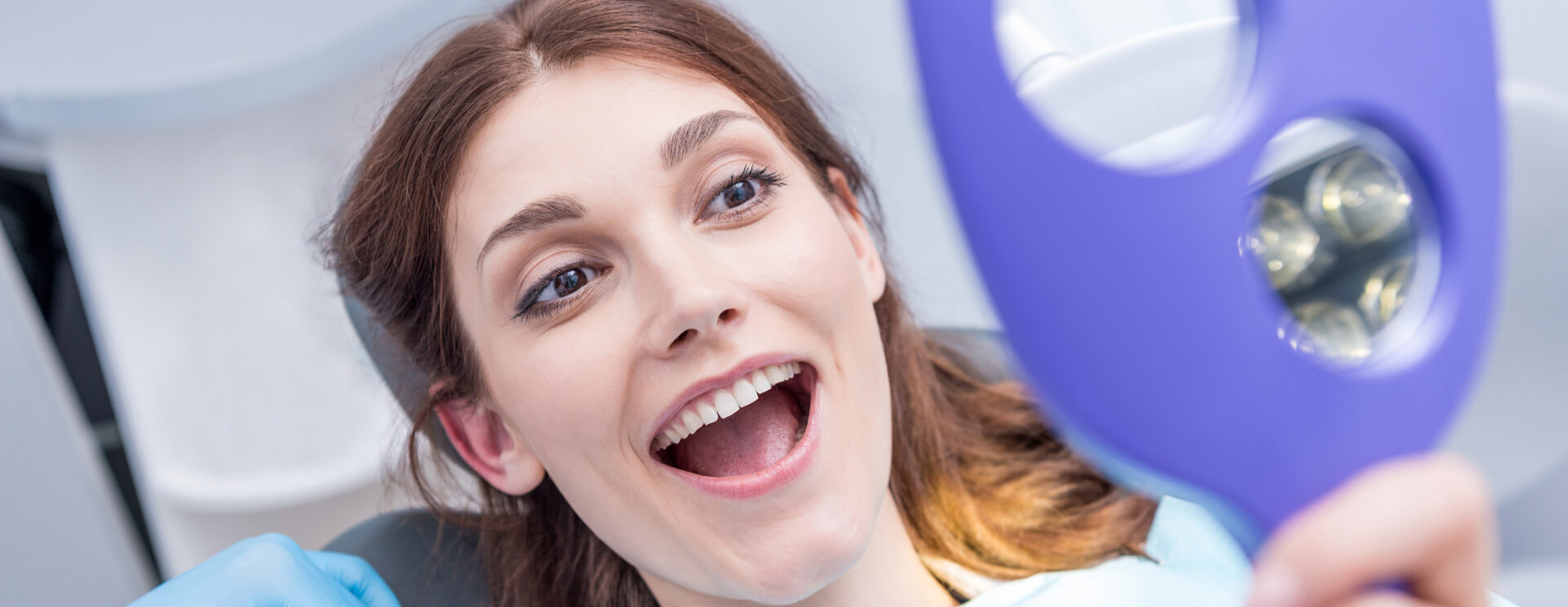 Young beautiful woman checking her new smile using a hand mirror
